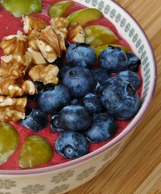 Smoothie-Bowl mit Himbeeren, Heidelbeeren, Mirabellen und Walnüssen