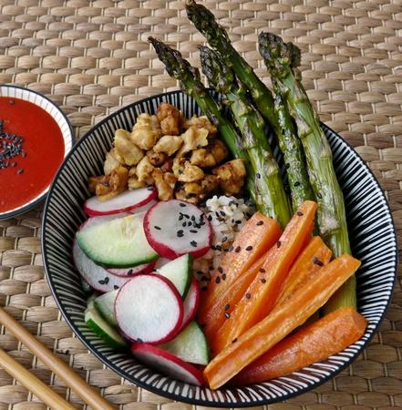 Bibimbap vegan: Reisschüssel mit grünem Spargel, Karotten, Gurken, Radieschen und Tempehbröseln