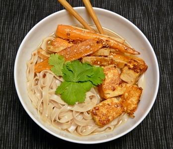 Vegane Reisbandnudelsuppe mit würziger Brühe, Sriracha-mariniertem Tofu und geröstetem Sesam-Wurzelgemüse