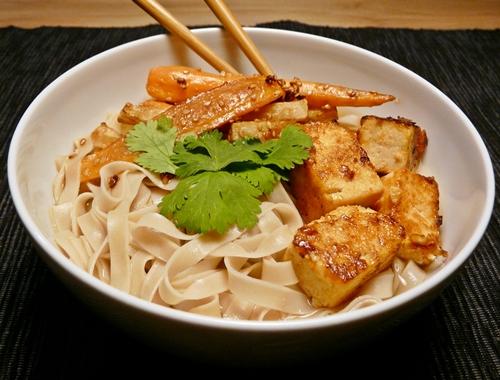 Vegane Reisbandnudelsuppe mit würziger Brühe, Sriracha-marinierte Tofuwürfeln und geröstetem Sesam-Wurzelgemüse